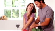 Smiling couple with red wine chopping vegetables video