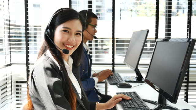 Smiling Customer support phone operator using headsets, Looking at camera video