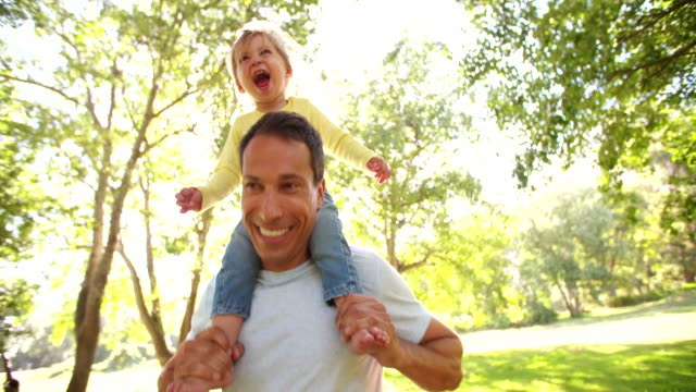 Smiling dad carrying his happy little girl on his shoulders video