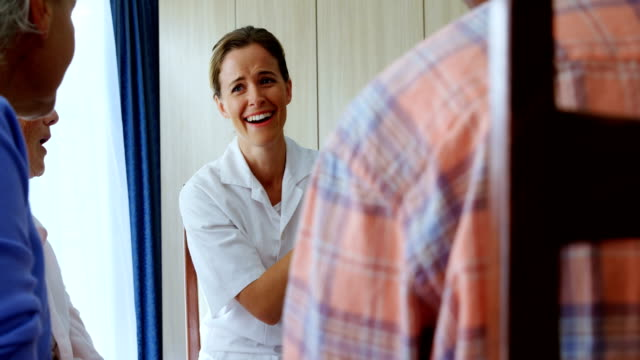 Smiling doctor explaining about medicine to senior people 4k video