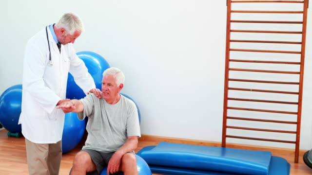 Smiling doctor helping patient move his arm and shoulder video