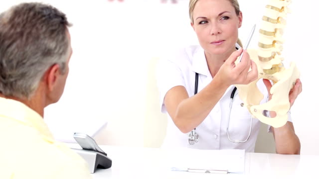 Smiling doctor showing spine model to her patient video