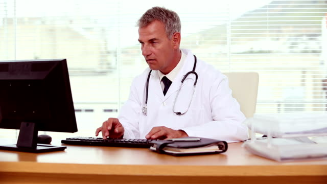 Smiling doctor using his computer video
