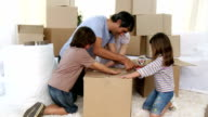 Smiling family packing boxes video