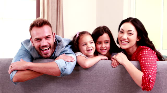 Smiling family posing on sofa video