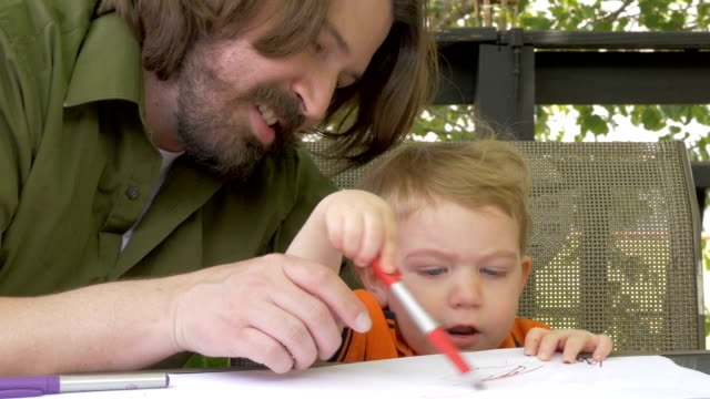 A smiling father and young toddler son drawing together on paper in slow motion video