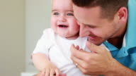 Smiling father tickling his baby boy video