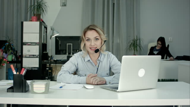 Smiling female consultant with headset presenting company services video
