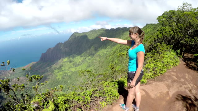 Smiling female hiker on mountaintop admiring view and pointing towards the ocean video