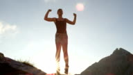 CLOSE UP: Smiling female in mountains jumping high and outstretching hands, legs video