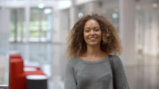 Smiling female university student walking into focus indoors video