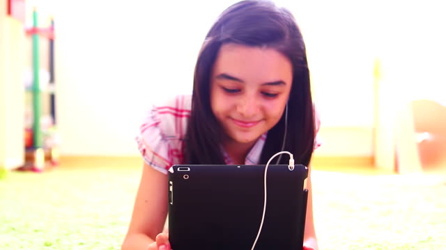 Smiling girl listening to music on digital tablet pc video