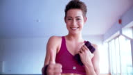 Smiling girl showing a thumb up sign while holding dumbells video
