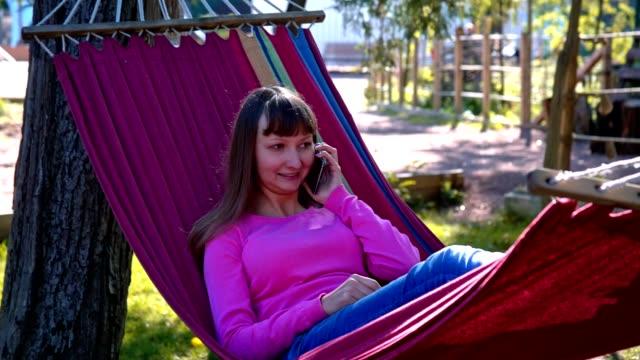 Smiling girl speaking on mobile phone on hammock video