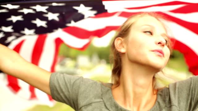 Smiling girl waving American flag. video