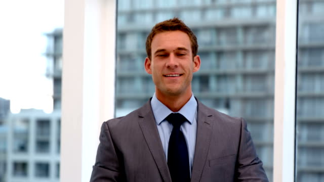 Smiling handsome businessman showing thumbs up video