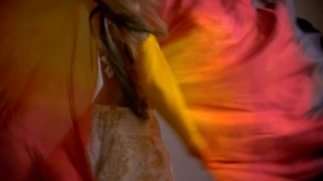 A smiling, happy woman twirling with flowing fabric as she turns and dances video