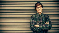 Smiling hipster man leaning against metal gate with copy space video
