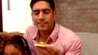 Smiling Hispanic family eating pizza in living room video