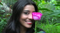 Smiling Hispanic Woman With Pink Flower video
