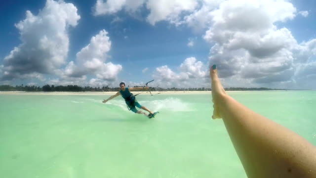 SLOW MOTION FPV: smiling kite surfer high five slapping while kiteboarding video