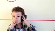 Smiling little boy talking on smartphone video