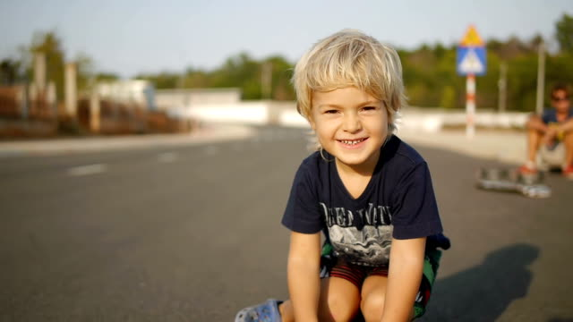 Smiling little child rides sitting on skateboard in slowmotion. Close up shot. video