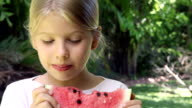 Smiling little girl eating red watermelon fruit outdoors video