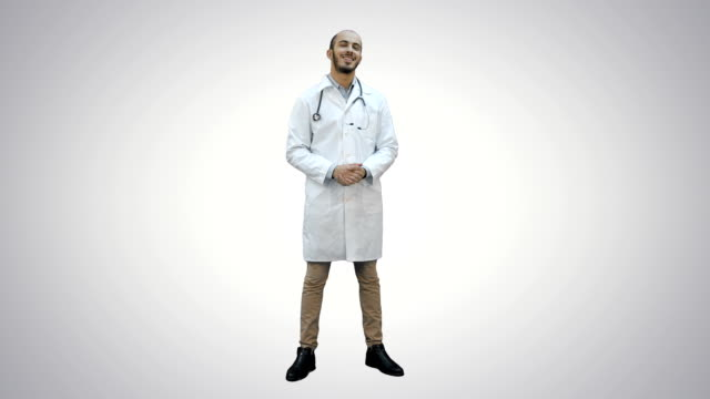 Smiling male doctor talking to the camera on white background video