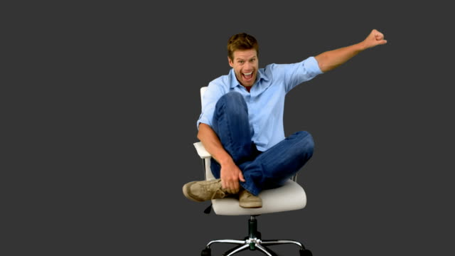Smiling man cheering and turning on swivel chair video