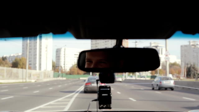 Smiling man in a mirror while driving car in a city. Handsome mans face. Traveling by car video
