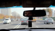 Smiling man in a mirror while driving car on a busy road in a city. Handsome mans face. Traveling by car video