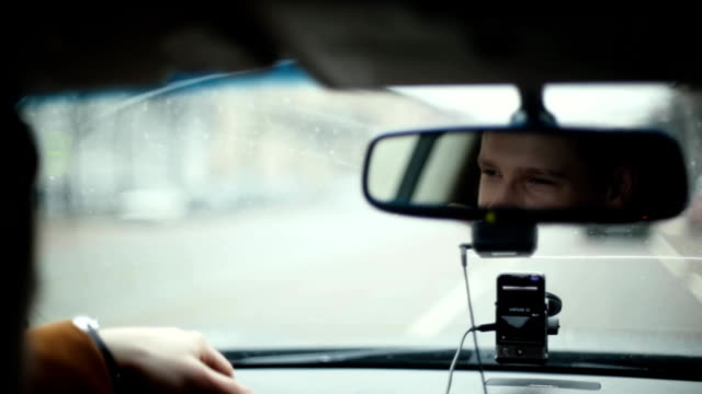 Smiling man in mirror while driving car in a city. Handsome mans face. Raindrops on the front window. Traveling by car video