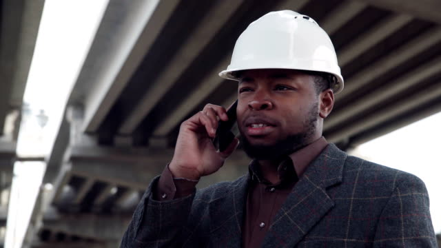 Smiling man in white hard hat on phone video