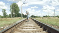 Smiling man jumping dancing on the railway tracks video