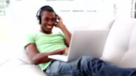 Smiling man lying on couch listening to music using laptop video