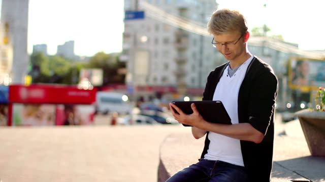 Smiling man reading electronic pad tablet pc, looking at camera video