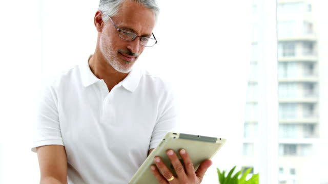Smiling man using his tablet video