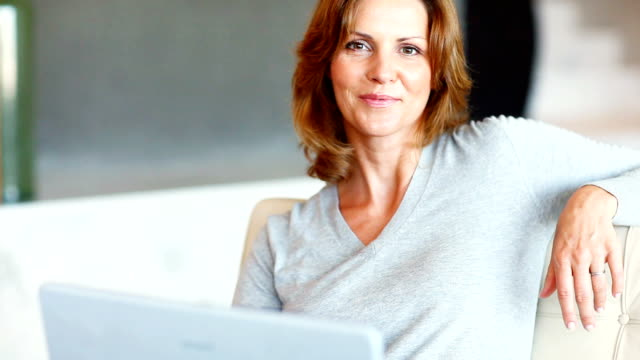 Smiling mature lady with her laptop video