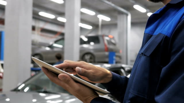 Smiling mechanic using a tablet pc at the repair garage service video