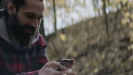 Smiling men text messaging on smart phone in forest video