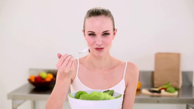 Smiling model eating a big bowl of salad video