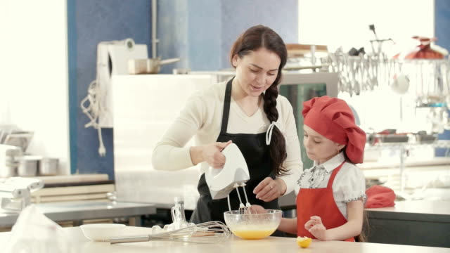 Smiling mother and daughter preparing dough together video