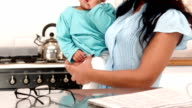 Smiling mother carrying baby boy in kitchen video