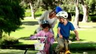 Smiling mother fastening the helmets of her children video