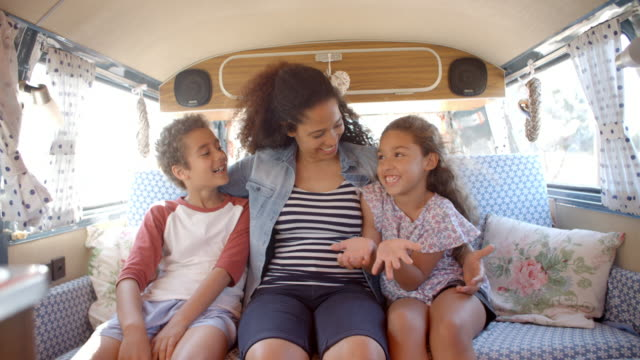 Smiling mum and kids travelling in the back of a camper van video