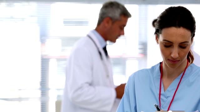 Smiling nurse holding clipboard video