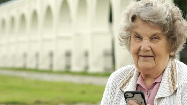 Smiling old woman holds silver smartphone outdoors video