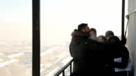 Smiling people make selfie with compact camera from the balcony on the background of a winter city video