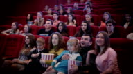Smiling people watching movie in cinema video